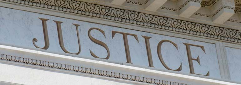 "Large engraving on building that says ""Justice"""
