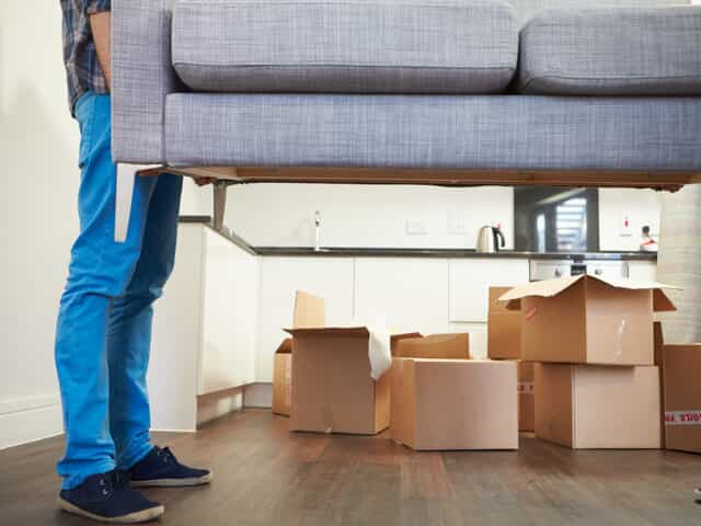 Man holding couch with packing boxes behind it representing relocation